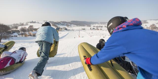 Deux personnes pratiquent l'airboard sur une piste de ski