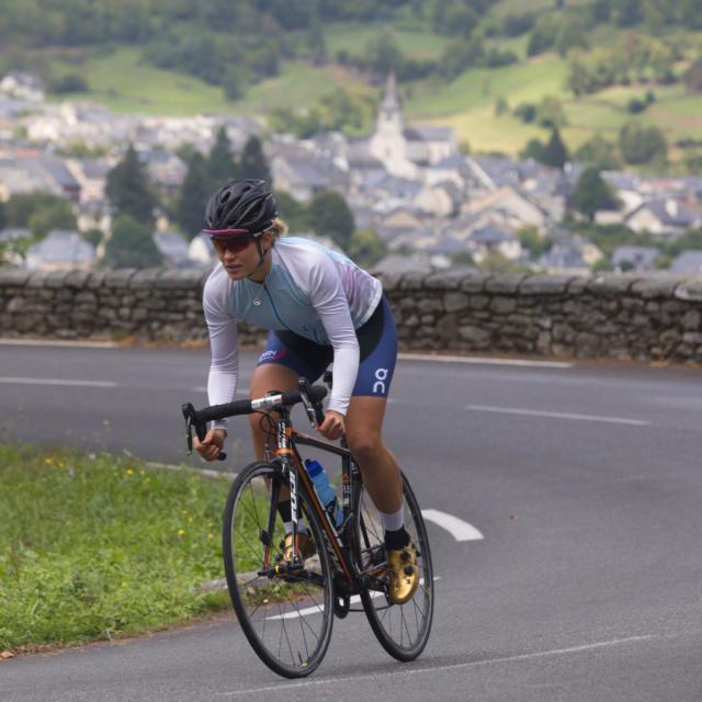 Une cycliste sur la route, village en arrière plan