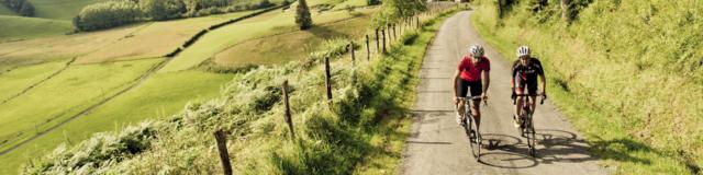 Deux cyclistes montent par une route de campagne