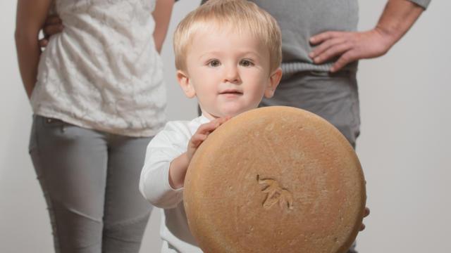 Un couple de producteurs de fromage de brebis, leur fils de tient une tomme de fromage de brebis au premier plan.
