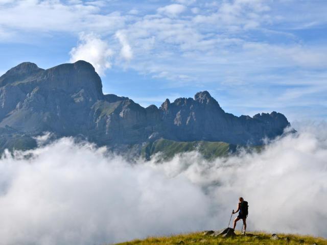 Randonneuse observe les aiguilles d'Ansabère dans les nuages