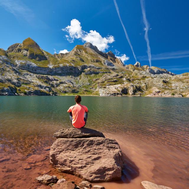 Randonneur assi sur une pierre au bord du lac d'Estaens