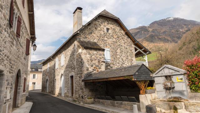Vue sur une maison traditionnelle béarnaise dans le village médiéval de Borce avec la montagne en fond