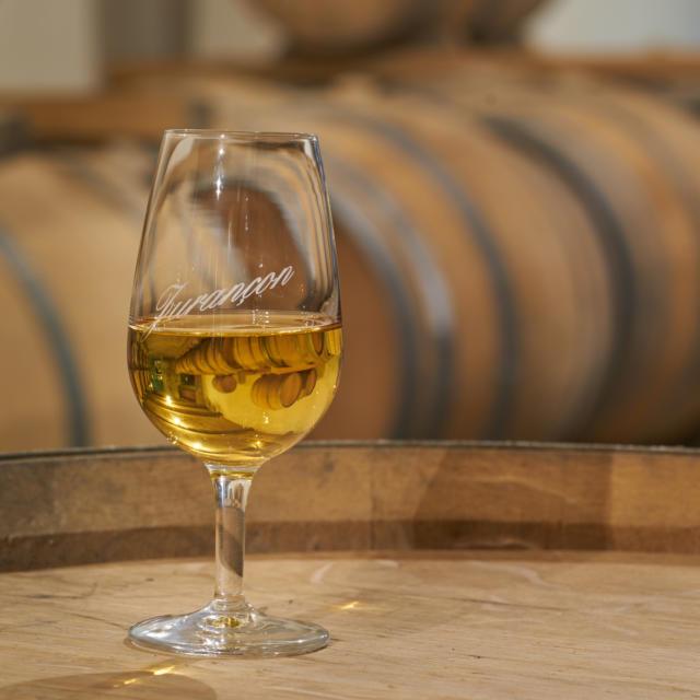 Un verre de vin de Jurançon est posé sur un tonneau dans un chai