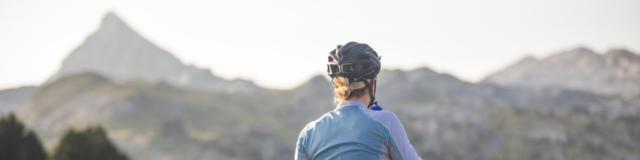 Une cycliste de dos fait une pause dans son ascension