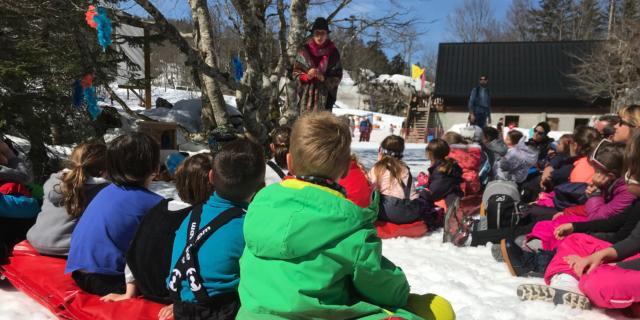 Enfants assis sur la neige écoutent des histoires dans la journée des enfants trappeurs